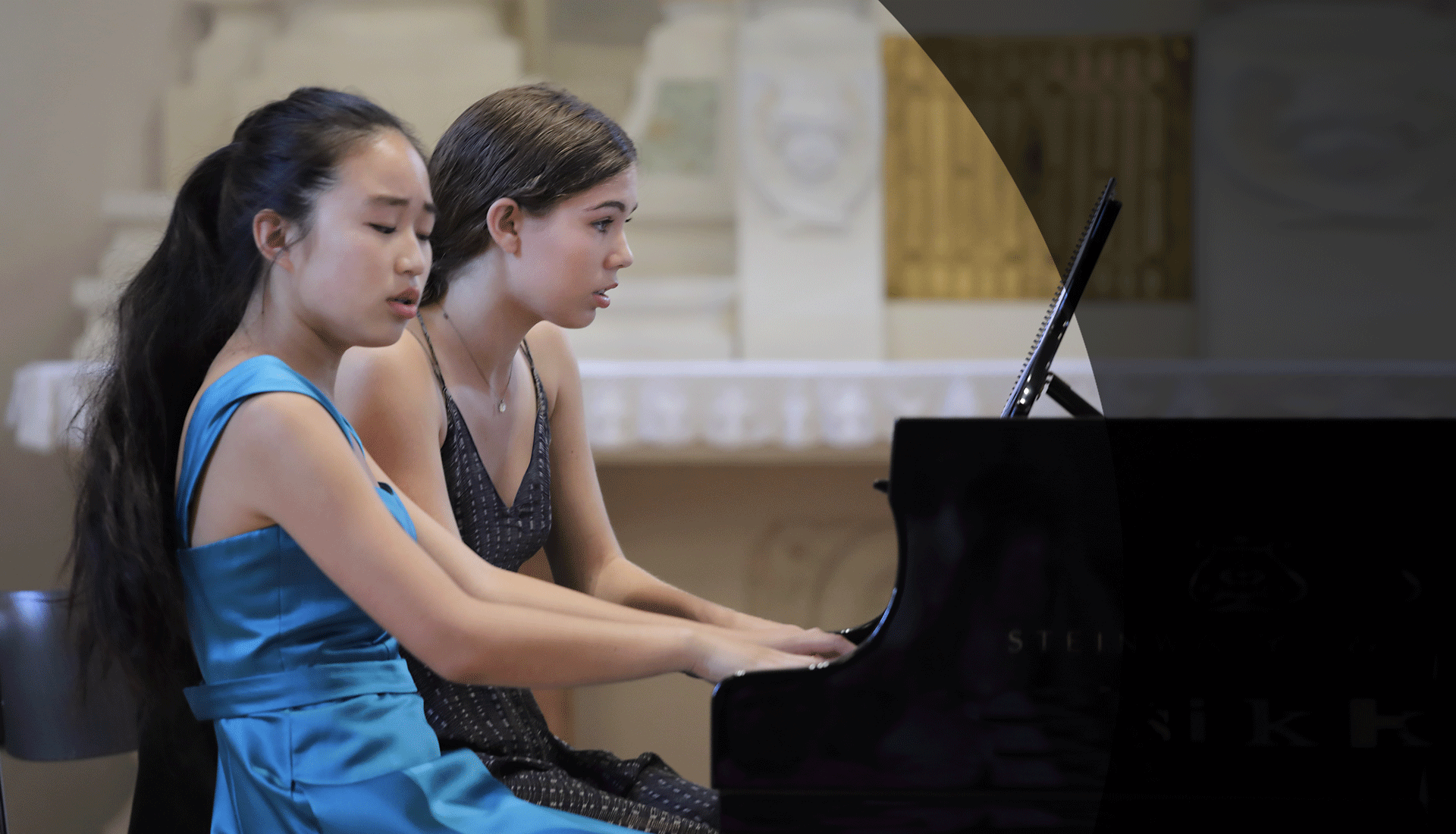 Two students playing a piano duo at the Borromeo Music Festival